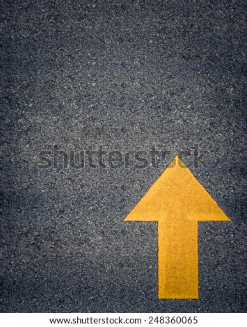Conceptual Image Of A Painted Yellow Arrow On A Road With Space For Text - stock photo