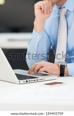 Conceptual image of a thoughtful businessman working on a laptop with his chin resting on one hand while typing information with the other, close up torso view of the hands and computer - stock photo