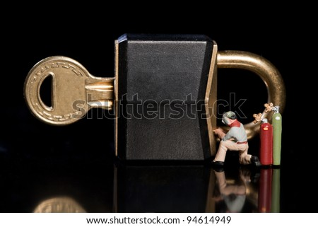 Conceptual image of a tiny miniature workman repairing a security breach to a padlock and key with an acetylene welder - stock photo