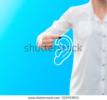 conceptual image of a woman holding a sketch of an ear - stock photo