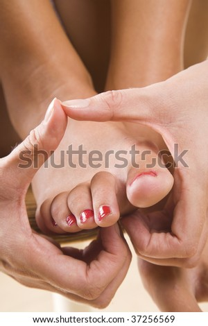 Conceptual image of a woman massaging her feet with her hands forming a heart shape - stock photo