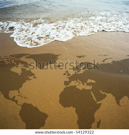 conceptual image of a world map on the beach - stock photo