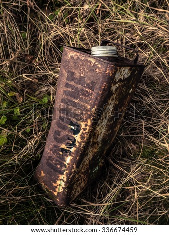 Conceptual Image Of An Old Rusty Gasoline Can Abandoned In The Undergrowth - stock photo