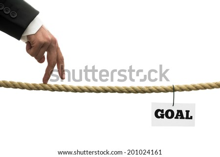 Conceptual image of business or life determination with a businessman walking his fingers along a length of rope or a tightrope towards his personal goals. - stock photo
