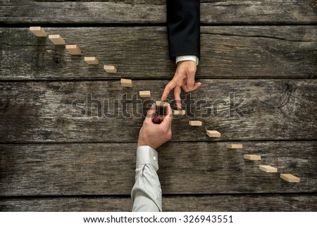 Conceptual image of business partnership and support - businessman supporting wooden step in a staircase made of pegs as his partner walks his fingers up towards growth, achievement and development. - stock photo