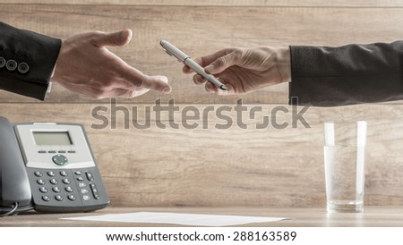Conceptual Image of Businessman Handing Over a Pen to His Business Partner to Sign the Contract or Employment Papers on Top of a Wooden Table with Telephone and Glass of Water. - stock photo