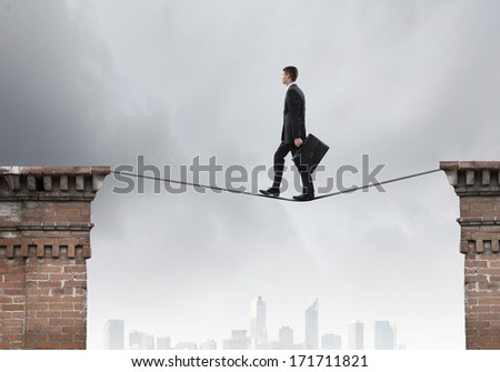 Conceptual image of businessman walking on rope above gap - stock photo