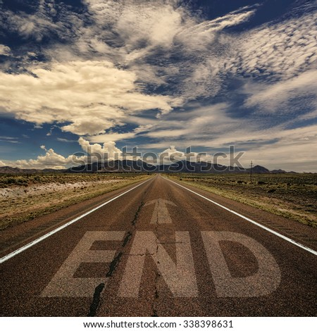 Conceptual image of desert road with the word end and arrow