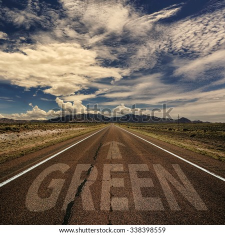Conceptual image of desert road with the word green and arrow