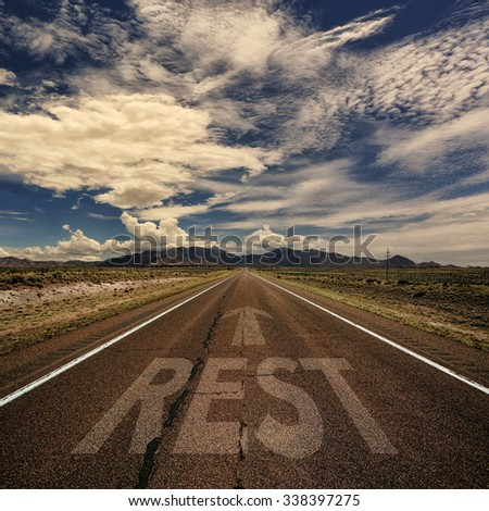 Conceptual image of desert road with the word rest and arrow