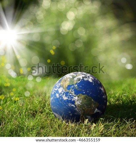 conceptual image of globe on green landscape and light. Furnished NASA image used for this image.
