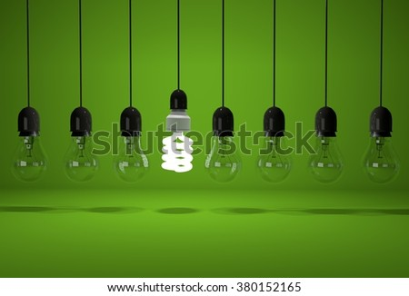 Conceptual image of glowing energy saving bulb and old dark bulbs on wires over green background