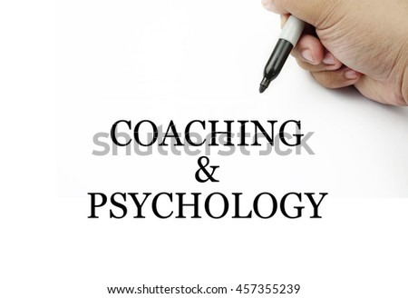 Conceptual image of handwriting COACHING & PSYCHOLOGY with the hand and pen isolated in white background.