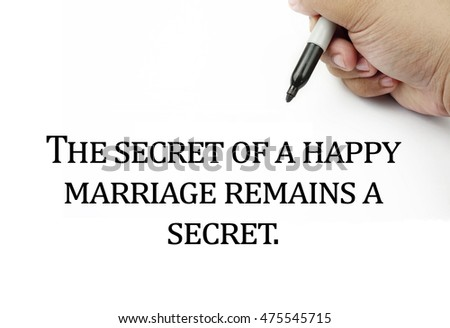 Conceptual image of handwriting quotes THE SECRET OF A HAPPY MARRIAGE REMAINS A SECRET with the hand and pen isolated in white background. copy space . Quotes concept.