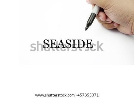 Conceptual image of handwriting SEASIDE with the hand and pen isolated in white background.