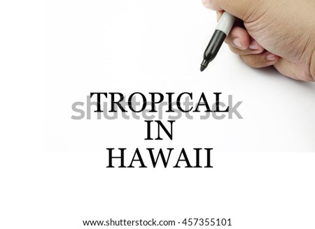 Conceptual image of handwriting TROPICAL IN HAWAII with the hand and pen isolated in white background.