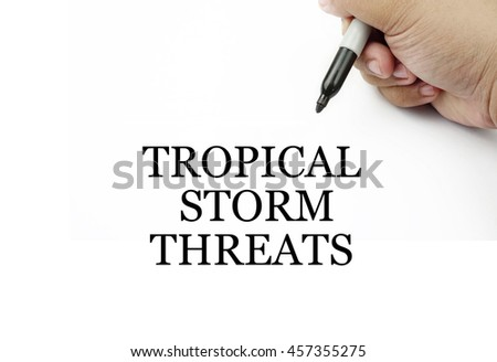 Conceptual image of handwriting TROPICAL STORM THREATS with the hand and pen isolated in white background.