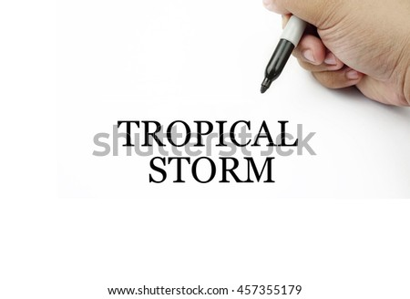 Conceptual image of handwriting TROPICAL STORM with the hand and pen isolated in white background.