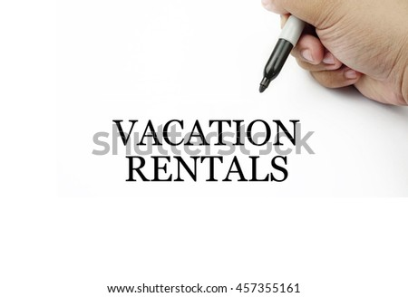 Conceptual image of handwriting VACATION RENTALS with the hand and pen isolated in white background.