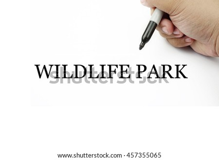 Conceptual image of handwriting WILDLIFE PARK with the hand and pen isolated in white background.
