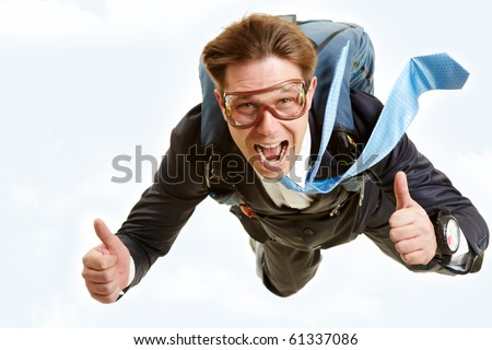 Conceptual image of happy man flying with parachute and showing thumbs up