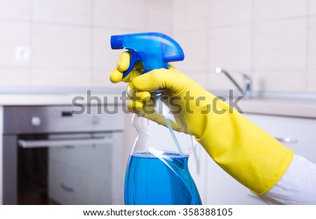 Conceptual image of kitchen cleaning. Close up of human hand with yellow rubber glove holding spray bottle with blue liquid. Clean kitchen countertop and stove in background