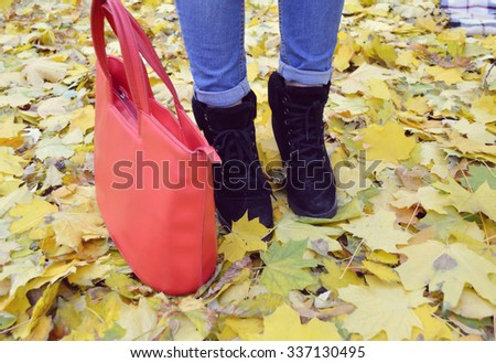 Conceptual image of legs in boots on the autumn leaves. Feet shoes walking in nature