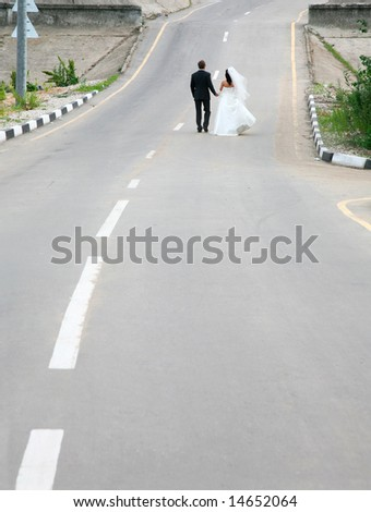 Conceptual image of newlyweds walking on road together