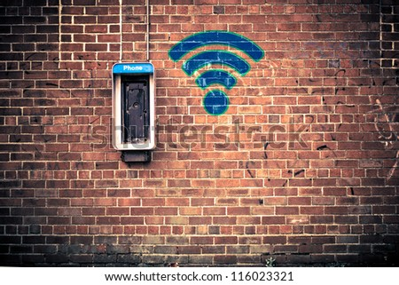 Conceptual image of out of use pay-phone on a grunge brick wall with icon for wi-fi hotspot on it