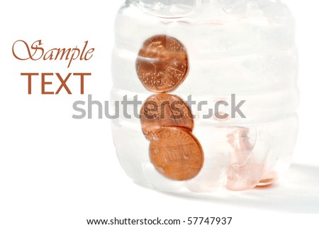 Conceptual image of pennies frozen in bottled water on white background with copy space. - stock photo