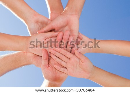 Conceptual image of people hands together with blue sky above - stock photo