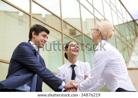 Conceptual image of people keeping hands on top of each other and laughing