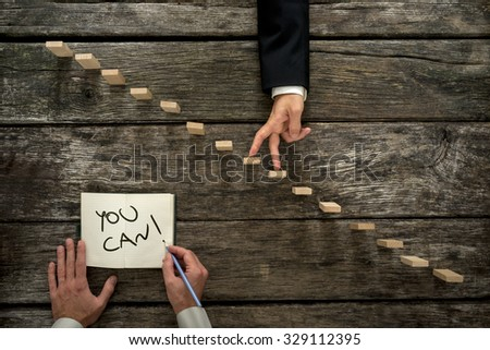 Conceptual image of personal growth and career development with businessman walking his fingers up wooden steps while his colleague or mentor encourages him with a You can message. - stock photo