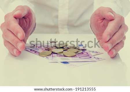 Conceptual image of protecting the Euro or your savings with a businessman cupping his hands on either side of a pile of 500 euro banknotes and coins safeguarding his investment and nest egg. - stock photo