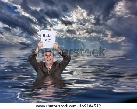 Conceptual image of senior businessman in suit up to waist in deep water worried about drowning in paperwork and holding help me document. Stormy clouds behind reflect in the ocean. - stock photo