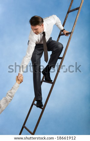 Conceptual image of successful businessman standing on ladder and giving hand to his partner - stock photo