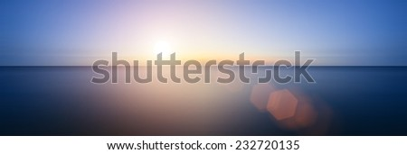 Conceptual image of sunrise sunset with added lens flare over still water ocean - stock photo