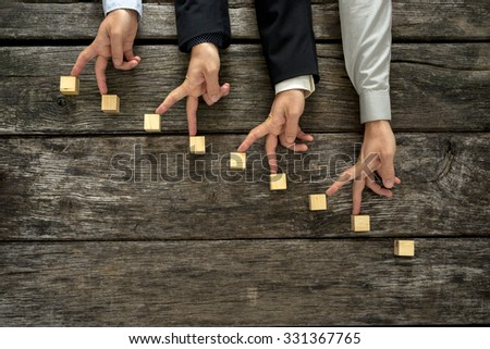 Conceptual image of teamwork and cooperation - four male hands walking their fingers up towards promotion and success on wooden blocks in the form of a staircase. - stock photo