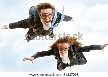 Conceptual image of young business partners flying with parachutes on their backs
