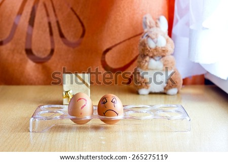 Conceptual image: what is happen eggs with sad smile face and question. Blurred background with golden gift box and easter bunny