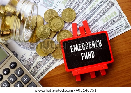 Conceptual image with EMERGENCY FUND words. Hundred dollar bills, coins and calculator on wooden background. - stock photo