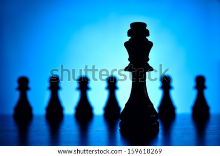 Conceptual image with focus to a a king chess piece in the foreground and a row of pawns behind with shallow dof silhouetted against a blue background with a highlight and copyspace - stock photo