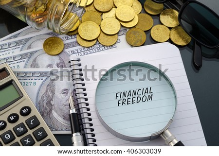 Conceptual image with hundred dollar bills, coins, calculator, notepad and magnifying glass with word Financial Freedom. - stock photo