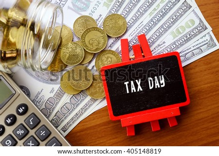 Conceptual image with TAX DAY words. Hundred dollar bills, coins and calculator on wooden background.