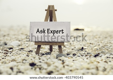 conceptual image with word ASK EXPERT on white canvas frame with wooden tripod stand.Blurred Clam shell and cockles background - stock photo