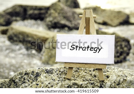 conceptual image with word STRATEGY on white canvas and wooden easel.Blurred rock and beach background at sunset. - stock photo