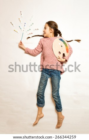 Conceptual isolated photo from top of cute girl lying on floor and drawing picture with oil paints - stock photo