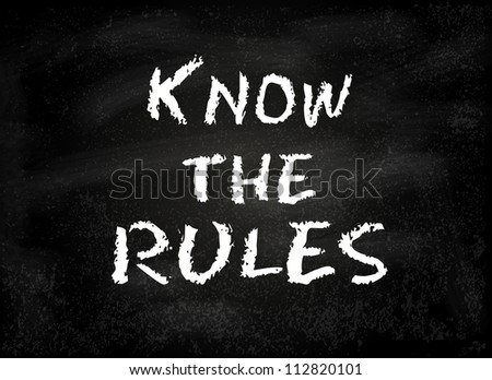 "Conceptual ""Know the rules"" text handwritten on black chalkboard blackboard. Slide template."