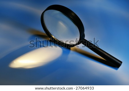 Conceptual magnifying glass on blue background