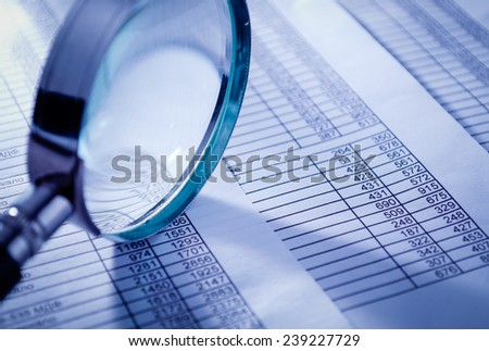 Conceptual Magnifying Glass on Top of Sales Invoice Reports, Emphasizing Scrutinizing Figures. - stock photo